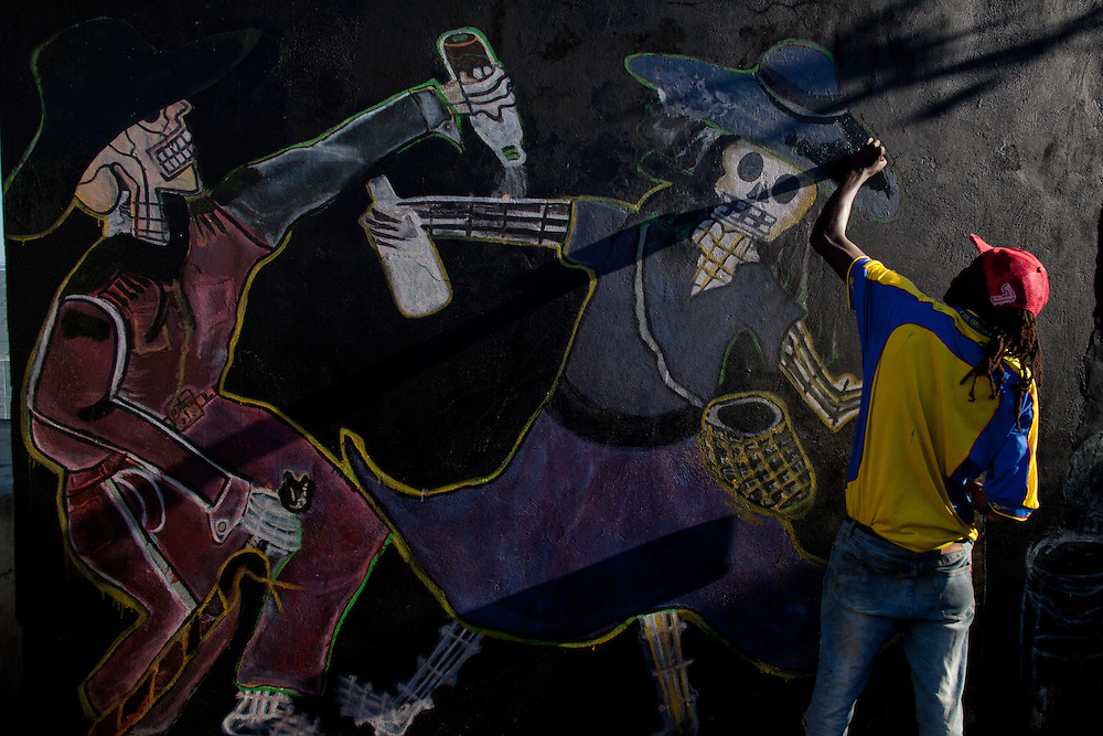 An artist touches up his painting of Baron Samedi and Maman Brigitte. Baron Samedi is the leader of the Gede and hiw wife, Maman Brigitte is protectress of the cemetery. November 1st and 2nd, known in Haiti as Gede, are a celebration of All Saints Day and All Souls Day. In Vodou, the Gede are the spirits that embody the powers of death and fertility. Practitioners come to the National Cemetery to honor their ancestors and to petition the spirits.