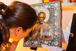 Sotheby's, London, November 21st 2014.  Sotheby's presents one of its strongest offerings of Russian paintings, icons and artworks as the renowned fine art  auction house celebrates its 25th year in Russia. Pictured: A Sotheby's employee examines the intricate detail of a silver-gilt and cloisonne enamel icon of St Nicholas the Miracleworker, expected to fetch between £50,000 - 70,000 at auction.