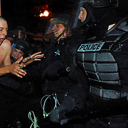 A protestor is wrapped up by riot police and taken into custody for failing to obey instructions to back up.