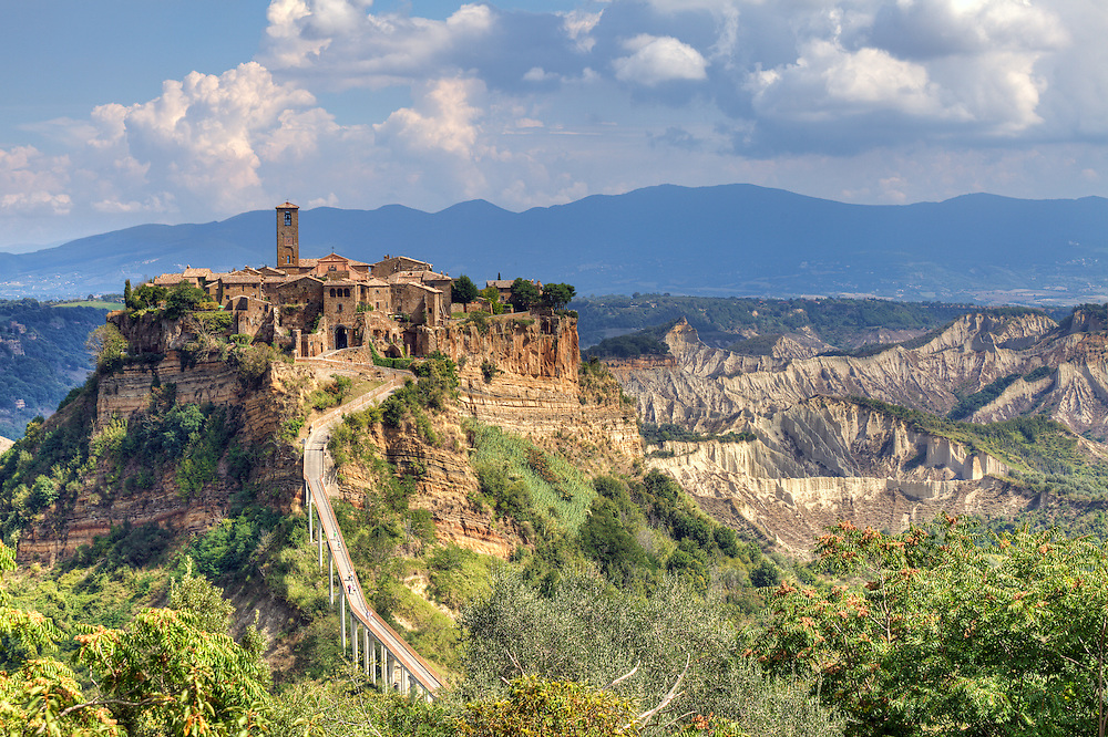 Founded by the Etruscans about 2.500 years ago, Civita is perched on top of a hill among the valleys formed by Chiaro and Torbido streams, the little town appears clinged to the edge of a cliff where it dominates the wide desolated valley made up of calanchi. This isolation is the result of a continuous erosion that makes the tufa rock becoming thinner and thinner on an unstable layer of clay and sand altered by wind and rain. In 1695 the beginning of Civita's decay was signed by a terrible earthquake which, causing serious damages to the roads and buildings, compelled many inhabitants to leave the city. The continuous sismic activities that followed in the course of the centuries, brought a long series of landslides; for this reason, Civita almost became completely desolated. Today, in fact, only a very small number of people live there who are determined to keep this little fragment of rock alive.