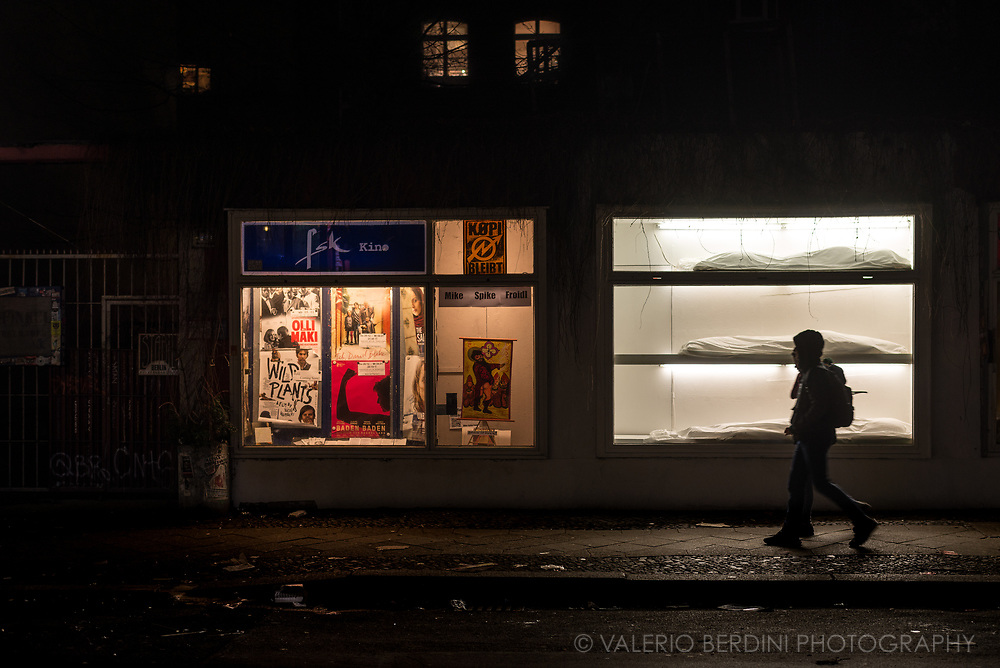 People walk past a lit window with white blankets covering unidentified objects. Berlin, 2017