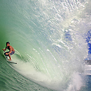 Local surfer deep in the barrel at Lagundri Bay