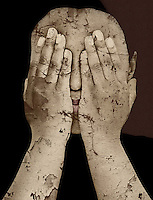 Woman holding her hands before her eyes.<br /> Black and white photo afterwards colored by hand.