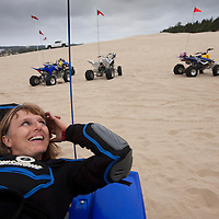 USA, Oregon, North Bend, Becky Selba rests while riding her ATV on sand dunes at Oregon Dunes National Recreation Area