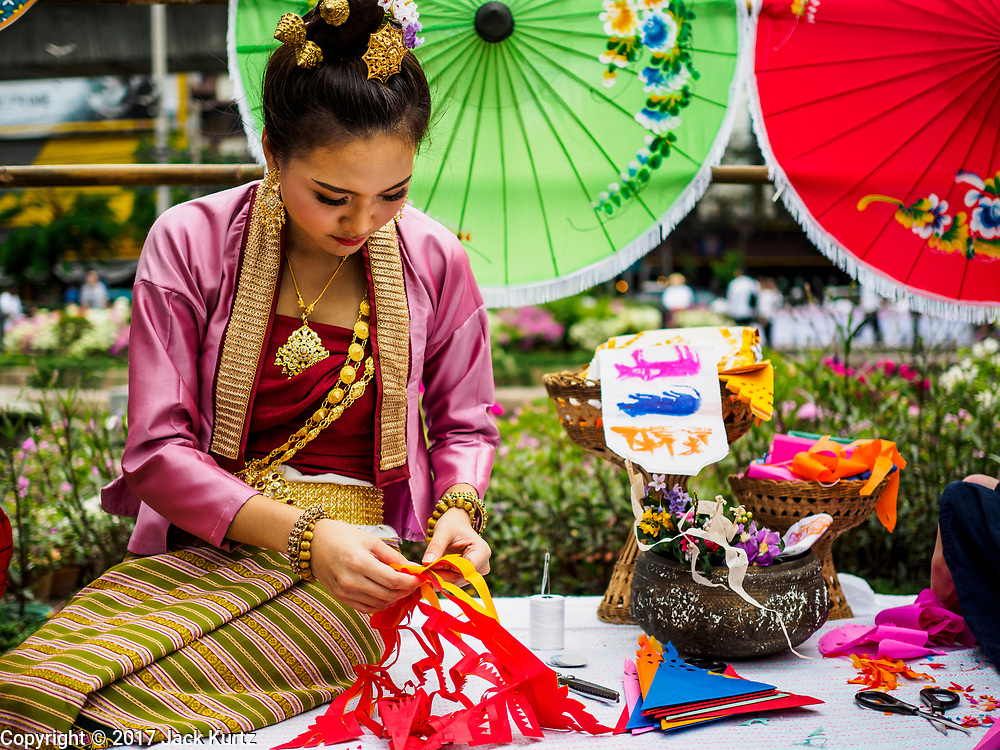 "08 APRIL 2017 - BANGKOK, THAILAND: A woman makes traditional Thai Songkran crafts at the ""Amazing Songkran"" festival in Benchasiri Park in Bangkok. The festival was sponsored by the Tourism Authority of Thailand to highlight the cultural aspects of Songkran. Songkran is celebrated in Thailand as the traditional New Year's Day from 13 to 16 April. Songkran is in the hottest time of the year in Thailand, at the end of the dry season and provides an excuse for people to cool off in friendly water fights that take place throughout the country. Songkran has been a national holiday since 1940, when Thailand moved the first day of the year to January 1. Songkran 2017 is expected to be more subdued than Songkran usually is because Thais are still mourning the October 2016 death of revered King Bhumibol Adulyadej.       PHOTO BY JACK KURTZ"