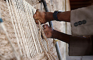 A man with leprosy assembles a straw floor mat at the All Africa Leprosy & Rehabilitation Training Center (ALERT) in Addis Ababa, Ethiopia on Thursday, December 8, 2005.
