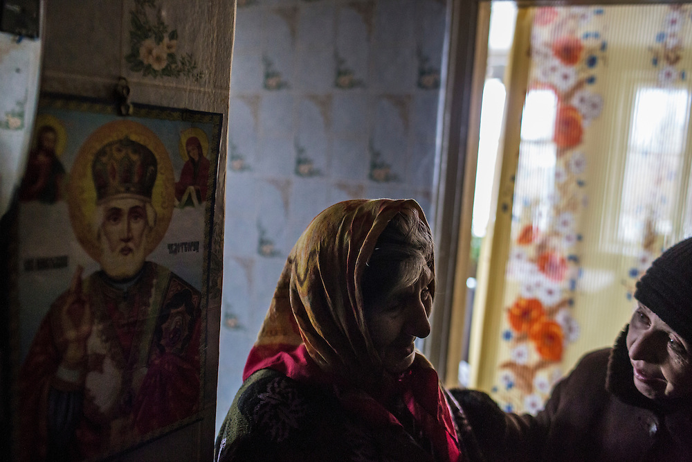 KOMUNAR, UKRAINE - JANUARY 27, 2015: Valentina Mozschagina, 80, is comforted by Valentina, right, a volunteer who coordinates humanitarian aide for local residents, in her home in Komunar, Ukraine. Mozschagina is the only caregiver for her disabled son Viktor, 58, and can often afford to eat only porridge. CREDIT: Brendan Hoffman for The New York Times