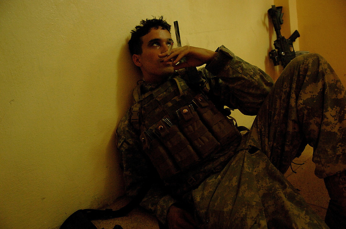 Exhausted from the heat, PFC Valentine Rodriquez from 1st Platoon Charlie Company 1/17th Infantry 172nd Stryker BDE Ft. Wainwright, Alaska, sits on the floor resting and smoking a cigarette at an Iraqi Police station June 21, 2006, during a patrol in Rissalo, Mosul, Iraq. — © TSgt Jeremy Lock/