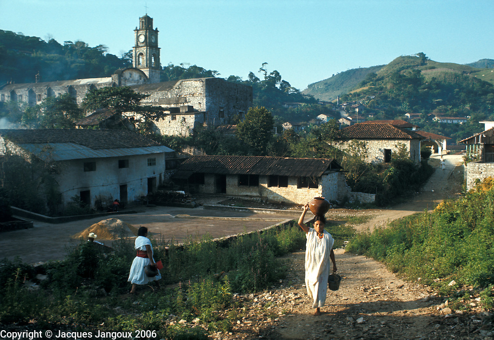 Mexico Puebla State Sierra de Puebla village Caxuacan Indian woman carrying water coming back from village well