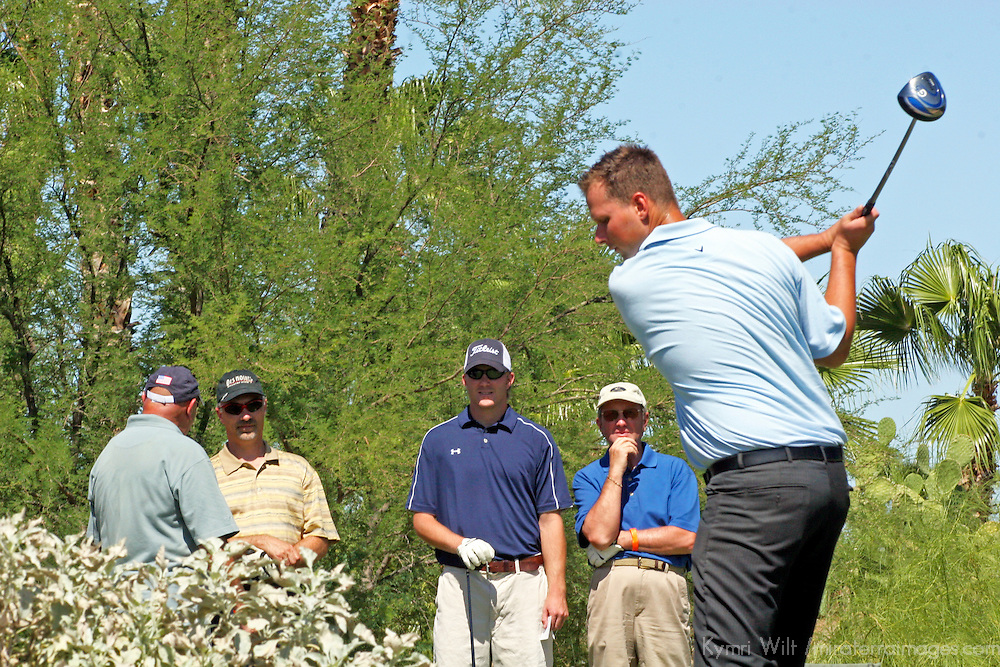 USA, Arizona, Fountain Hills.  Group of male golfers watch tee off.