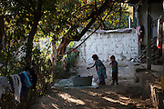 5 year old Omeda (MDR TB) plays outside with water together with her cousin at her aunt's home, where she is staying for a week while her parents are visiting family in another district.