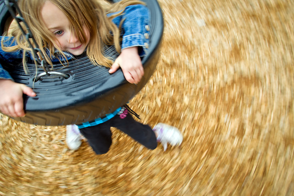 Jade Miller, 6, takes a spin on a tire swing while on an outing Friday with her family to G.O. Phippeny Park in Coeur d'Alene.
