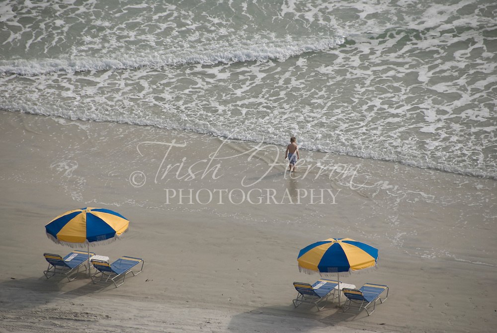 A small boy stands at the edge of the water / surf near two blue and yellow beach umbrellas.