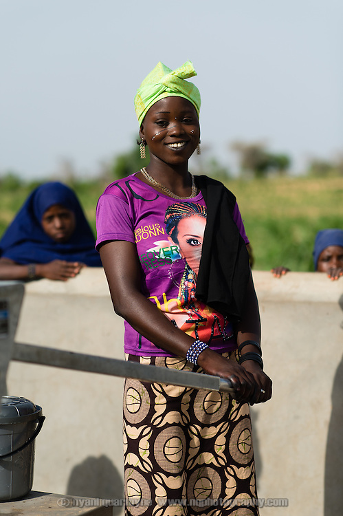 "Talatou Noura, 17, at a WaterAid pump in the village of Kanwa-Maraki in the Zinder Region of Niger on 25 July 2013. When asked about the pump she said, ""I am happy now that we have enough water drinking, cooking washing dishes and bathing the children."" She is a mother of one, and has a daughter who is not quite a year old."