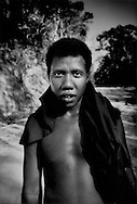 This young man is not African, his very deep roots are in Southeast Asia.  Young Batek Negrito man on a new logging road that cuts into the forest along the Taman Negara National Park boundary to log right up to the edge of the park next to Kuala Koh, Kelantan, (Peninsular) Malaysia.  The Batek Negritos use this road to get to a riverside settlement of semi-nomads on a tributary to the Lebir River.  Almost all the land north of the park, their traditional homeland, has been clear cut and converted to oil palm cultivation.  Much of that oil will be used to make bio fuel.