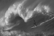A surfer rides a giant wave at the southern end of Lyall Bay, Wellington, New Zealand
