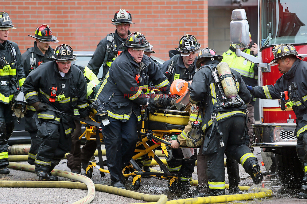 03/26/14-Boston,MA. Boston firefighters carry one of their own from 296 Beacon St. after a large wind-whipped fire claimed the Back Bay building and injured several today, March 26, 2014. Staff photo by Mark Garfinkel