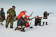 Canadian Rangers patrol rides snowmobiles for a shooting drill next to their camp in Baring Bay on Devon Island, Nunavut, during Nunalivut 2012 sovereignty exercise in arctic Canada. 20 April 2012. At this time they were equipped with antediluvian Lee Enfield rifles that were later replaced with more modern weaponry. But as shown, uniform regulations are pretty laxly enforced as Inuits Rangers wisely complement army issued clothings with seculars furs and animal skins, still unmatched by synthetic fibers.<br /> Rangers are army units that mix local volunteers, here Inuits, and professional military acting as eyes and ears in the most remote areas of northern Canada.