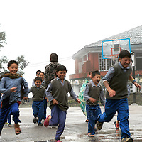 Tibetan students play in the rain during a break from class at TCV, the Tibetan Children's Village. McLeod Ganj, Dharamsala, India. 7/29/05. This is a school for Tibetan exile children run by the Tibetan government in exile.