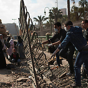 Egyptian volunteers remove broken fences and garbage left over from 18 days of protest in the area around Tahrir Square February 12, 2011 in Cairo, Egypt. The day after the revolution toppled the regime of President Hosni Mubarak, Egyptians continued to celebrate and began to focus on rebuilding their city and society. (Photo by Scott Nelson)