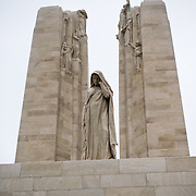 "The weeping woman or better known as ""Mother Canada mourning her dead"" in front of the twin white pylons of the ‪Canadian National Vimy Memorial‬ dedicated to the memory of Canadian Expeditionary Force members killed in World War one. The monument is situated at a 100 hectare preserved battlefield with wartime tunnels, trenches, craters and unexploded munitions. The memorial designed by Walter Seymour Allward opened in 1936."