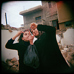 Nadia Al-Akhrass and her daughter Nour look at a piece of film that was found in the rubble of the home of their relatives, who were killed in the war between Israel and Hezbollah, Aytaroun, Southern Lebanon, Oct. 23, 2006.