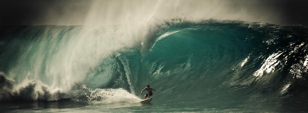 Male surfer bottom turns on a huge wave, Bonsai Pipeline, Oahu, Hawaii, USA.