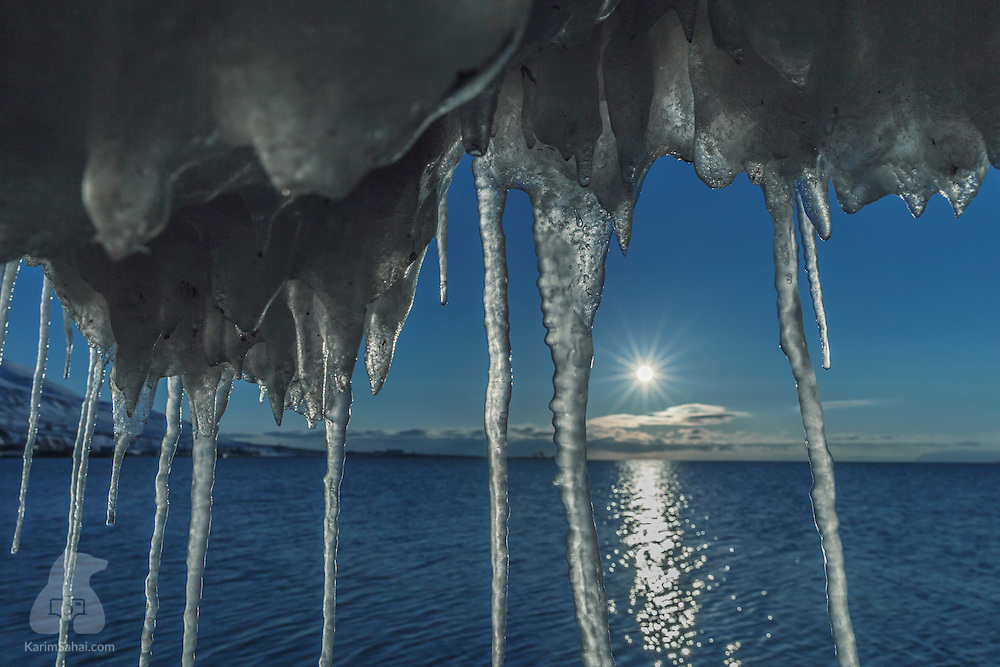The midnight sun shines between icicles on the beach near Isfjorden, Longyearbyen, Svalbard