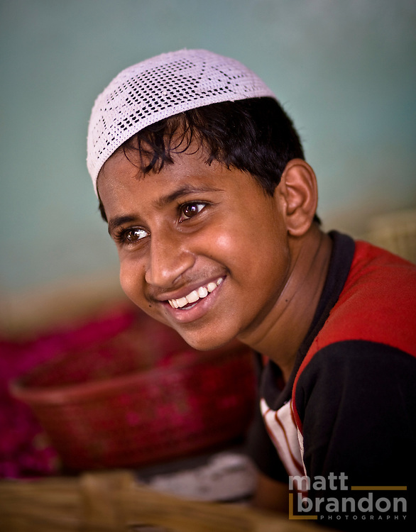 A young boy smiles for the camera inside a mosque at Nizamuddin.