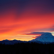 A fiery winter sunrise colors the sky surrounding Mount Rainier, the tallest mountain in Washington state. At right, Mount Rainier, with a summit elevation of 14,411 feet (4,392 meters), casts its own shadow on the sky, a phenomenon that occurs when the sky is covered by mid-altitude clouds around the time of the winter solstice. At left, smaller peaks do the same, resulting in bands of light known as crepuscular rays.
