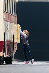 London, March 13th 2016. The annual St Patrick's Day Parade takes place in the Capital with various groups from the Irish community as well as contingents from other ethnicities taking part in a procession from Green Park to Trafalgar Square.  PICTURED: A child polishes a vintage bus prior to the procession. &copy;Paul Davey<br /> FOR LICENCING CONTACT: Paul Davey +44 (0) 7966 016 296 paul@pauldaveycreative.co.uk