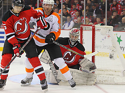 Mar 13, 2013; Newark, NJ, USA; New Jersey Devils goalie Johan Hedberg (1) looks for the puck through a screen by Philadelphia Flyers right wing Scott Hartnell (19) while New Jersey Devils defenseman Adam Larsson (5) defends during the second period at the Prudential Center.