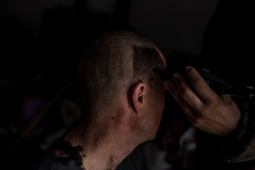 A Ukrainian soldier gets his head shaved on Saturday, March 19, 2016 in Shyrokyne, Ukraine.