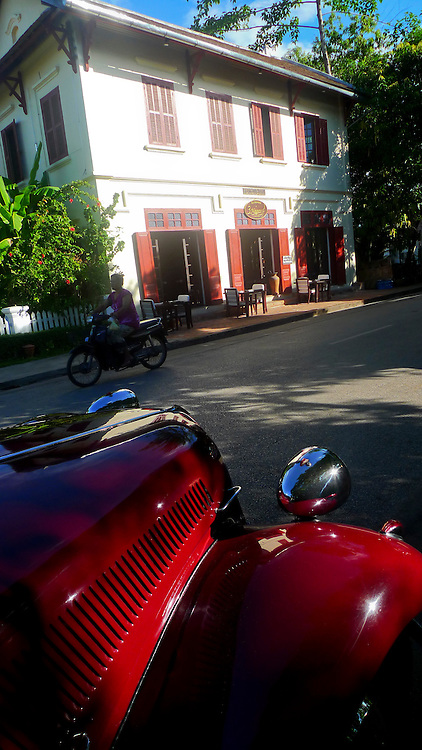 A vintage red car parks in front of restaurants in the streets of Luang Prabang. @ Martine Perret. 24 May 2010