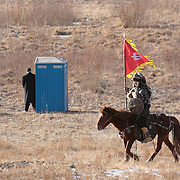 A US Secret service agent stands by a restroom as a rider in  traditional Mongolian wear passes-by at Ikh Tenger Monday, November 21, 2005, in Ulan Bator, Mongolia...Photo by Khue Bui