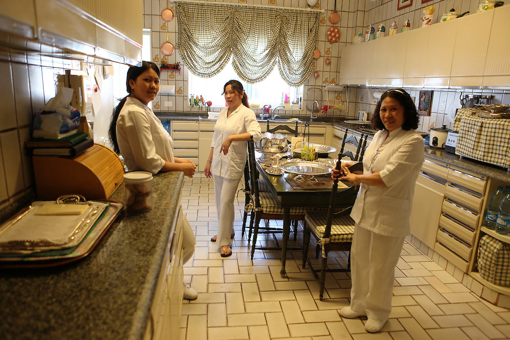 Filipino women all employed in one home take a break from work.