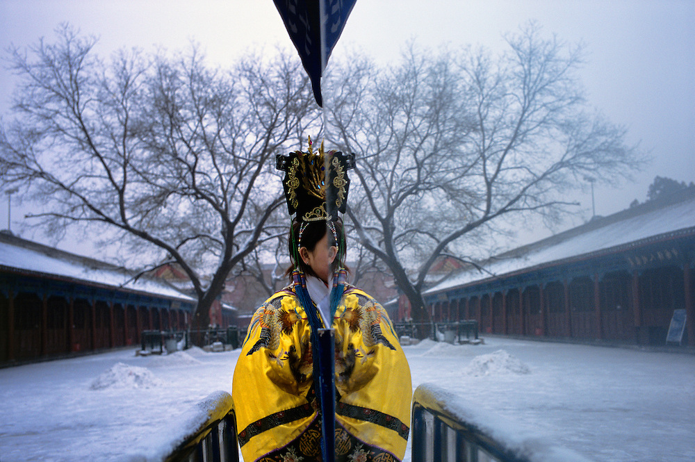 A young woman dressed in Imperial-style costume for a souvenir photograph, passing behind a mirror in the Forbidden City (for checking make-up and costume), after the first snowfall of winter...From China [sur]real © Mark Henley..