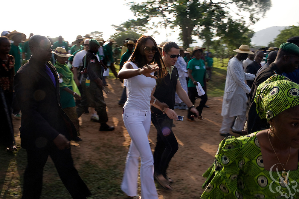 "Super model Naomi Campbell is flanked by security guards as she participates in a tree planting ceremony as part of the 3rd annual ThisDay festival July 11, 2008 in Abuja, Nigeria. The ThisDay festival, themed ""Africa Rising"", is an effort to raise awareness of African issues and promote positive images of Africa using music, fashion and culture.."