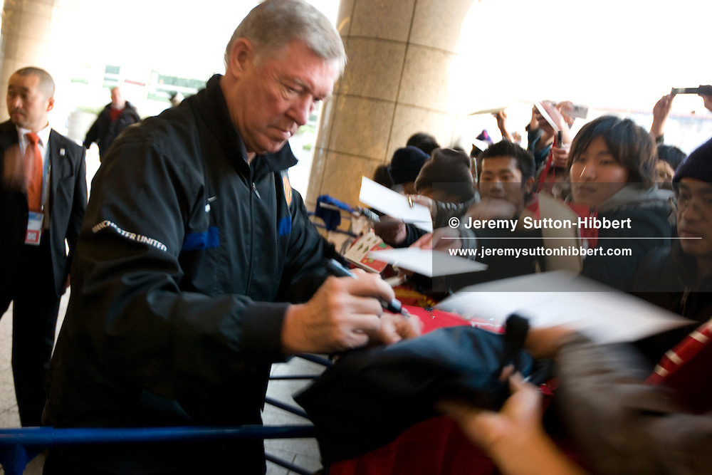 Watched over by both Japanese and manchester United security guards, manager Sir Alex Ferguson signs autographs for the Japanese Manchester United supporters out side the Pan Pacifico Hotel, where the Manchester United football team is staying whilst in Japan to compete in the FIFA Club World Cup,  in Yokohama, Japan, Tuesday 16th December 2008.