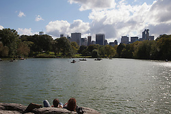 people in Central Park enjoying the view of the lake and skyline on a fall day