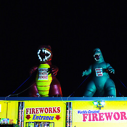 Inflatable creatures tied down to the roof draw attention to this fireworks stand near the Indiana/Illinois border in Whiting, IN as a guy in a matching yellow shirt loiters.