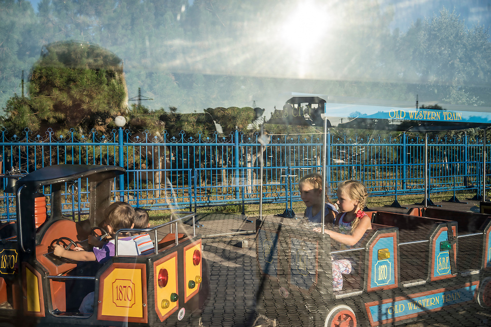 MARIUPOL, UKRAINE - AUGUST 30, 2015: Children ride a small train at the Mariupol Extreme Park, an amusement park in Mariupol, Ukraine. Despite the front line being a relatively short distance away, Mariupol was lively on a warm summer weekend, with little evidence that people expect the fighting to advance this far. CREDIT: Brendan Hoffman for The New York Times