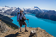 From stunning Panorama Ridge, Tom admires the vibrant turquoise color of Garibaldi Lake, which comes from glacial flour suspended in meltwater from Sphinx and Sentinel Glaciers. Above the lake rise Mount Garibaldi (2678 m or 8786 ft), a potentially active stratovolcano. Garibaldi Provincial Park is east of the Sea to Sky Highway (Route 99) between Squamish and Whistler in the Coast Range, British Columbia, Canada. A hiking loop to Garibaldi Lake via Taylor Meadows Campground is 11 miles (18k) round trip, with 3010 ft (850m) gain. Panorama Ridge is 6 miles (10k) RT with 2066 ft (630m) gain from either Taylor Meadows or Garibaldi Lake Campground (or 17 miles RT with 5100 ft gain from Rubble Creek parking lot). For licensing options, please inquire.