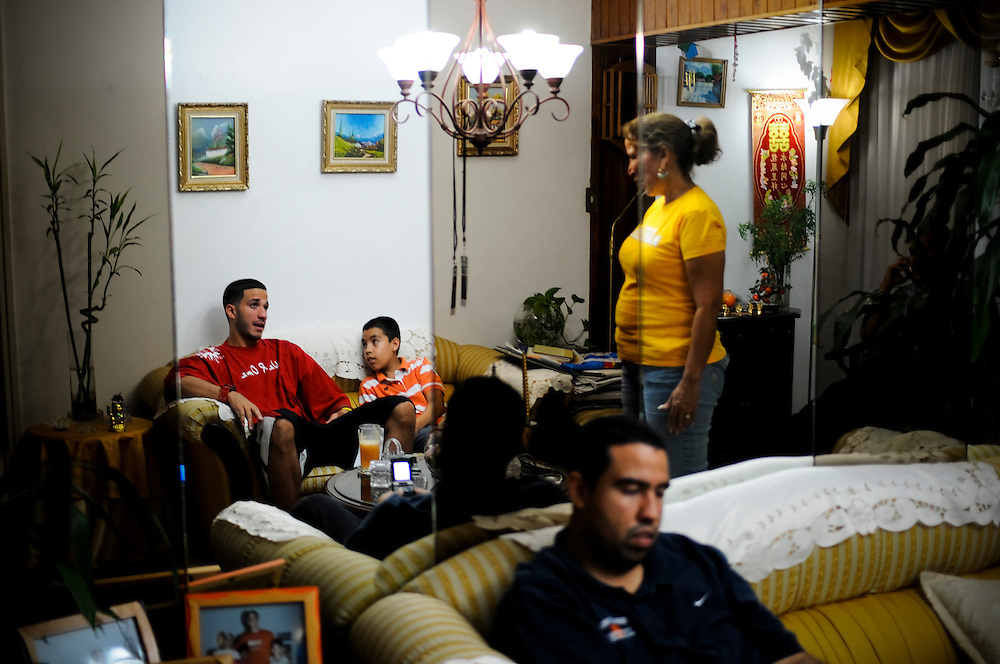 Maryland basketball player, Greivis Vasquez (top left in red) talks with his mom, Ivis Rodriguez (in yellow shirt), nephew, Adrian Sanoja Jr. (striped shirt) and brother, Adrian Sanoja (front in blue) at his mother's home in Caracas, Venezuela.