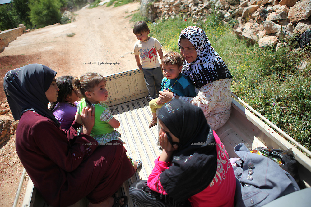 innersyrische Flüchtlinge auf einem Pickup in Basheria. Das Dorf Basheria nach dem kürzlichen Angriff der Regierungstruppen. Zahlreiche Häuser wurden dabei beschossen oder von angesteckt. Mehr als 20 Menschen wurden getötet. Nutztiere der Bewohner erschossen.