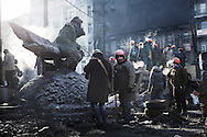 Perched on pile of tires and charred police bus, anti government protester stands<br />  guard on Hrushevskoho street barricades near Maidan Square during standoff with riot police while a truce was agreed.  Monument of Valeriy Lobanovskyi outside Dynamo Stadium entrance was wrapped by protester for protection,  in Kiev, 27 January 2014.
