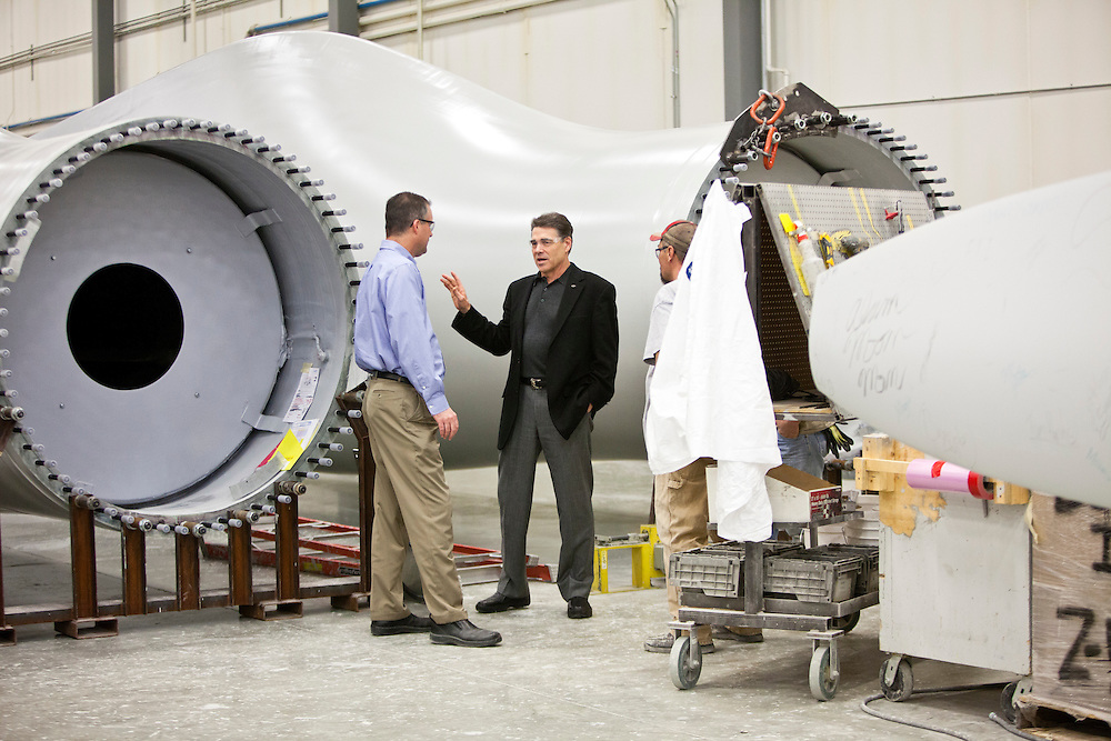 Republican presidential candidate Rick Perry, center, stands near wind turbine blades as he speaks to employees before an employee town hall at TPI Composites on Thursday, December 22, 2011 in Newton, IA.