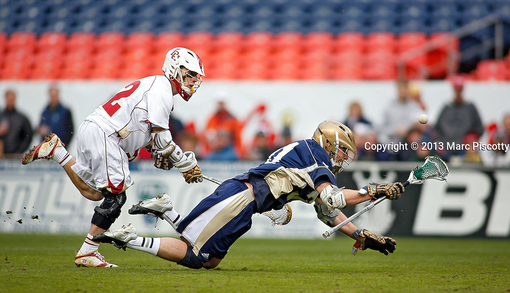 SHOT 3/16/13 4:50:52 PM - Denver's Chase Carraro #32 trips up Notre Dame's Liam O'Connor #31 as the two chase after a loose ball during their college lacrosse game at the Whitman's Sampler Mile High Classic at Sports Authority Field at Mile High in Denver, Co. on Saturday March 16, 2013. Notre Dame won the game 13-12 in overtime. (Photo by Marc Piscotty / © 2013)