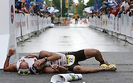 Craig Alexander (right) and Chris Lieto collapse at the finish line after Alexander overtook Lieto in the final straight-away to win the men's professional division of the the Ironman 70.3 Boise race. The race featured a 1.2 mile swim in Lucky Peak Reservoir, a 56-mile bike ride, and 13.1-mile run finishing in downtown Boise.