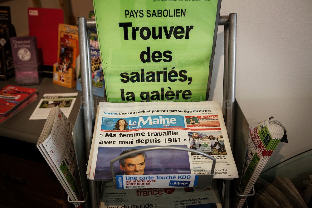 """News stand at the cafe with local papers featuring Francois Fillon statement  on French TV about his wife's salary. Above, the poster display """"Finding some workers, the hassle"""" about jobs opportunities in the region. Reactions in Solesmes, Sarthe, where Penelope Fillon is member of the city council. She is under judiciary investigation for getting paid a generous salary from public funds that were allocated to her husband Francois Fillon as an MP for the central Sarthe region to pay for parliamentary staff. According to French news paper, she was paid without producing significant work as parliamentary assistant. Francois Fillon is candidate for the incoming French presidential election in April."""
